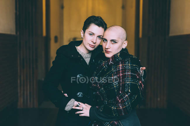 Portrait of young lesbian couple with arms around each other in hallway — Stock Photo