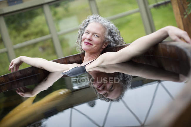 Portrait of mature woman relaxing in hot tub at eco retreat — Stock Photo
