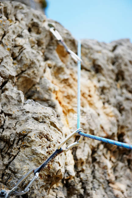 Low angle view of carabiner and stones — Stock Photo