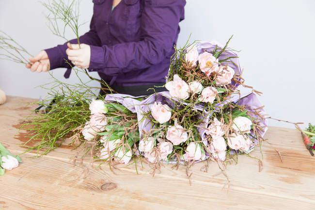 Mujer arreglando rosas en floristerías - foto de stock