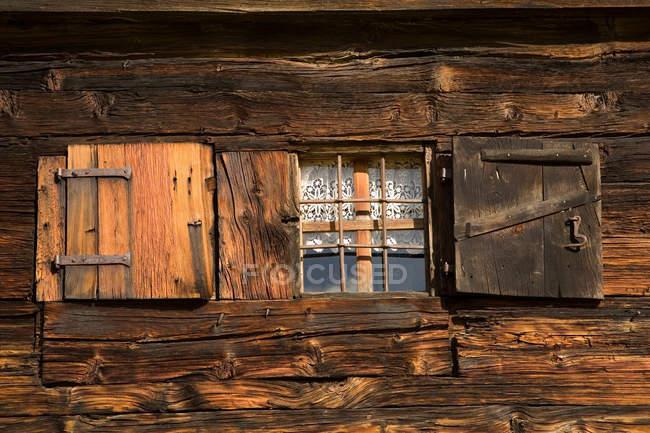 Zellenförmiges Fenster an Holzwand — Stockfoto