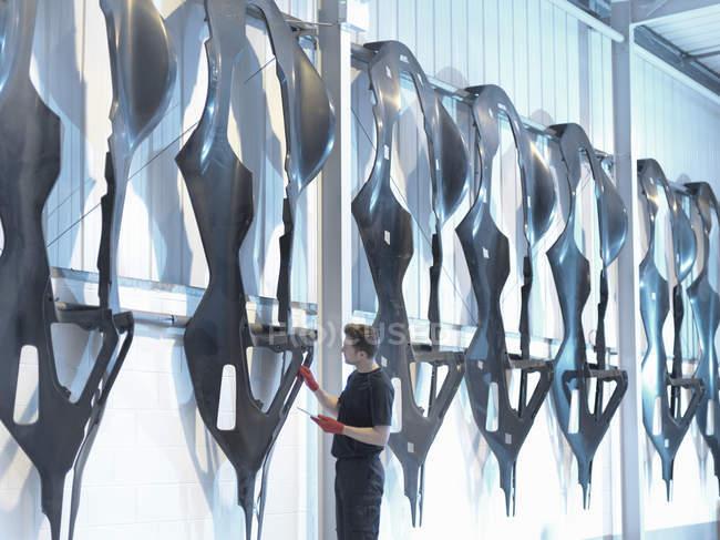 Ingegnere che ispeziona gusci di carrozzeria in fibra di carbonio in fabbrica di auto da corsa — Foto stock