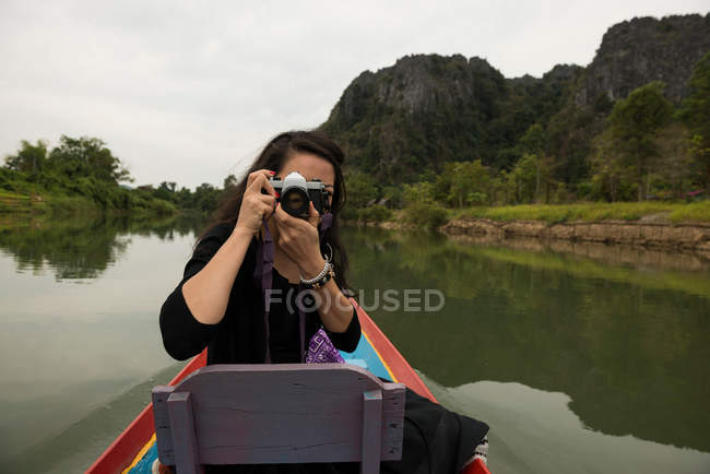 Woman taking photograph on boat on Nam Song River, Vang Vieng, Laos — Stock Photo