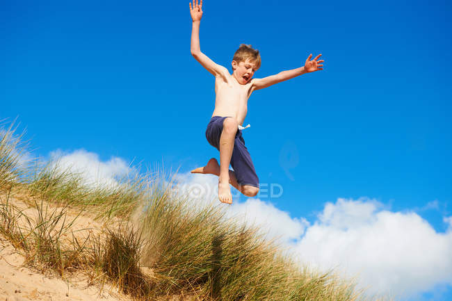 Happy boy jumping on beach — Stock Photo