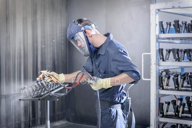Pintura de los trabajadores que pulverizan piezas de automóviles en la fábrica de pinturas de aerosol - foto de stock