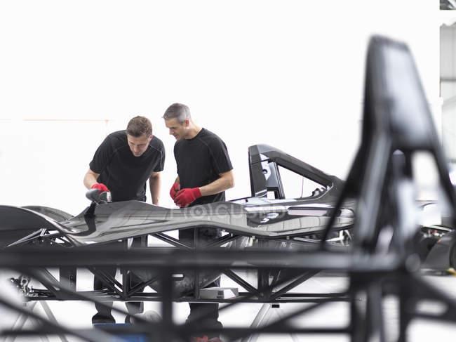 Ingenieure prüfen Kohlenstoff-Faser-Auto body Shell in Sportwagen-Fabrik — Stockfoto