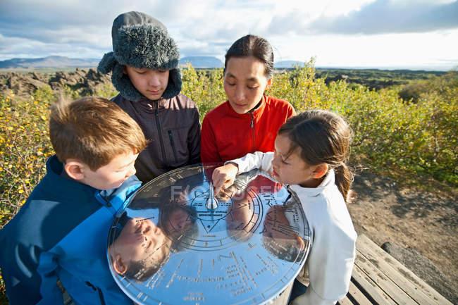 Family examining metal sundial — Stock Photo