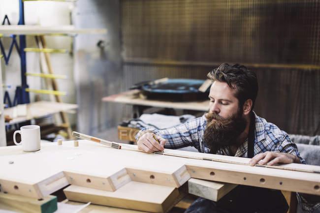 Schnappschuss eines erwachsenen Handwerkers beim Messen von Holzkomponenten in Orgelwerkstatt — Stockfoto