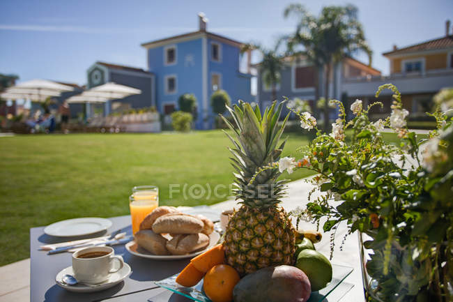 Ripe fruits on table at holiday resort with houses on background — Stock Photo