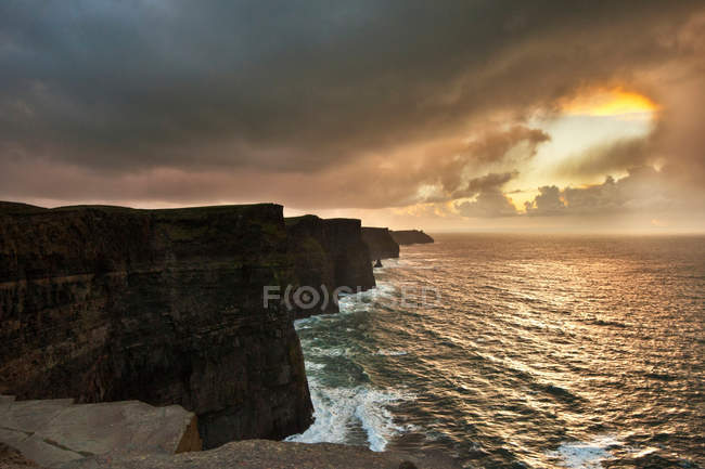 Colorful clouds over coastal cliffs — Stock Photo