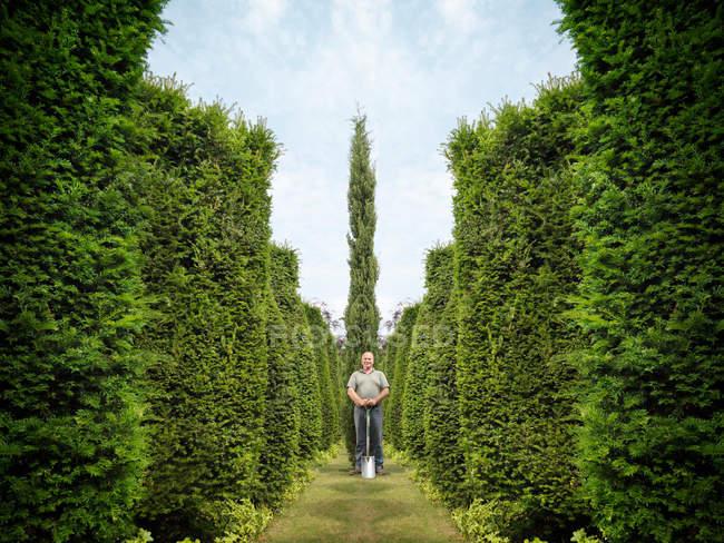 Gärtner mit Spaten und immergrünen Bäumen — Stockfoto