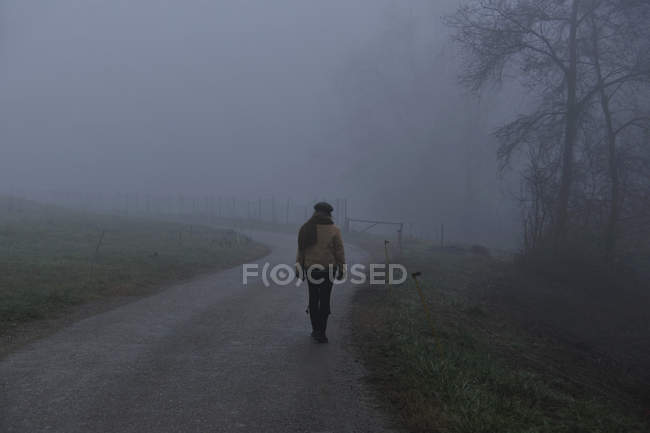 Woman walking on foggy rural road — Stock Photo