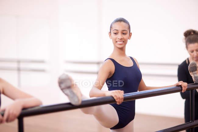 Teenage ballerinas practicing at barre — Stock Photo