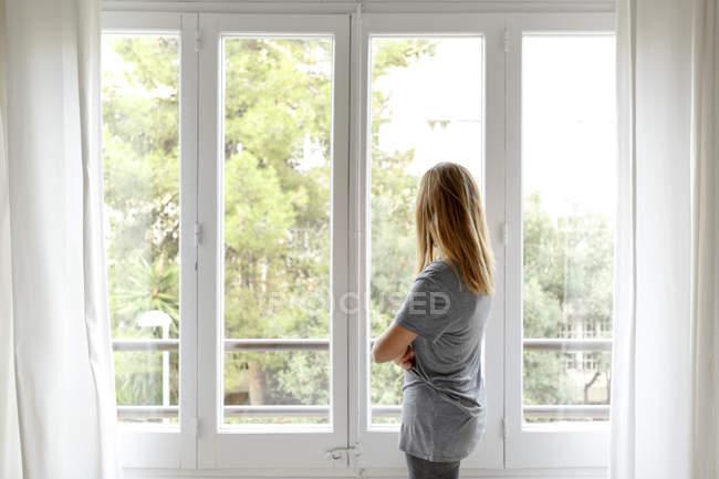 Rückansicht der jungen Frau zu Hause Blick aus Fenster — Stockfoto