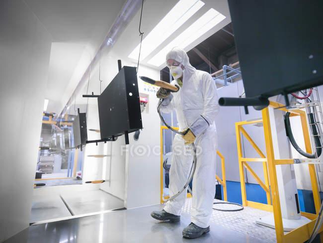 Piezas de recubrimiento en polvo de trabajador masculino en cabina de pintura en fábrica de chapa metálica - foto de stock