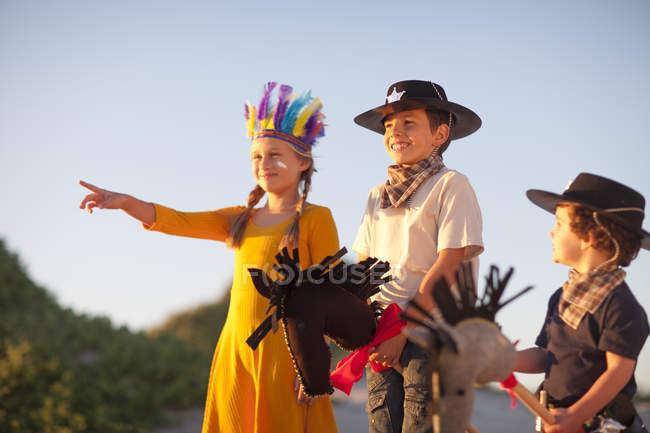 Трое детей, одетых как коренные американцы и ковбои, указывающие с песчаных дюн — стоковое фото