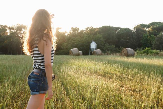 Mujer de pie en el campo de hierba - foto de stock