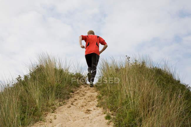 Вид сзади на человека, выбегающего на обочину — стоковое фото