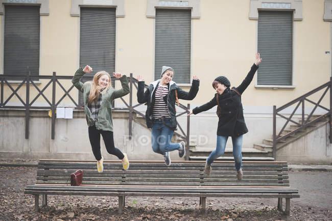 Три сестры прыгают на скамейке в парке — стоковое фото