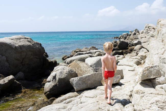 Молодий хлопець, що ходить на скелях біля морської води — стокове фото
