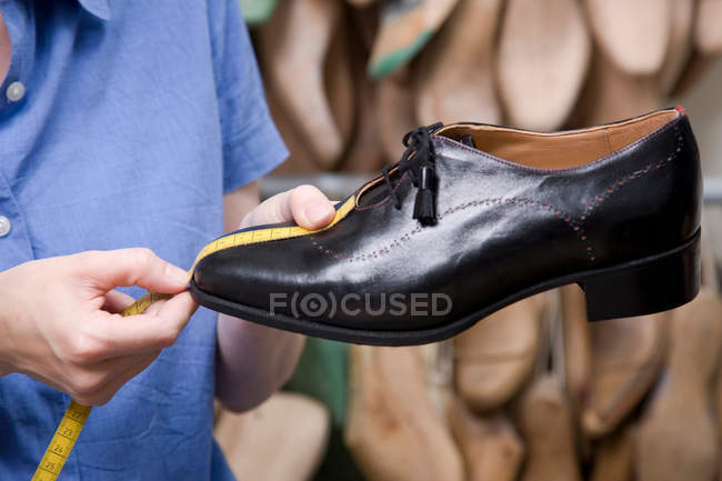 Worker hands measuring shoe, close up — Stock Photo