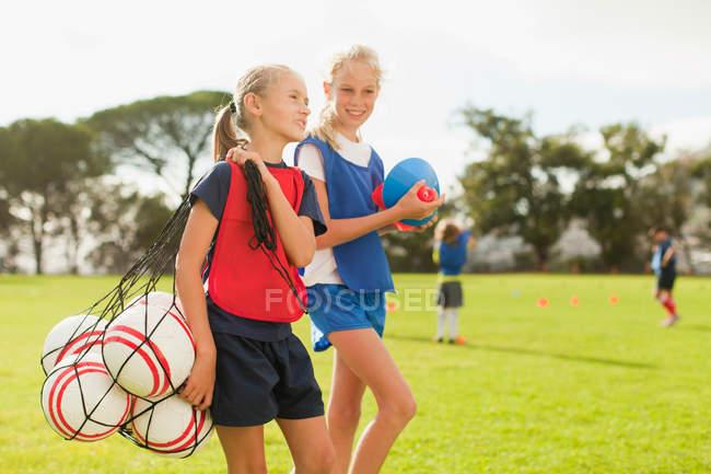 Mädchen trägt Fußballbälle auf dem Spielfeld — Stockfoto