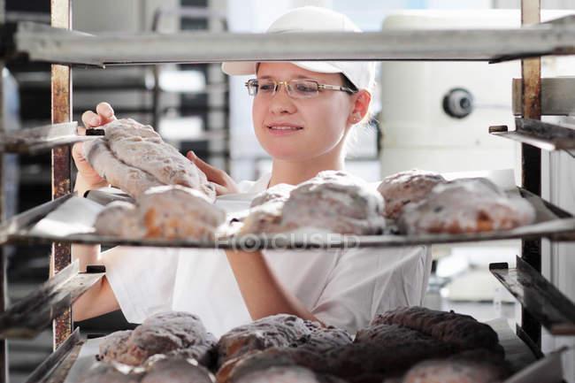 Baker, colocar a massa de pão na assadeira — Fotografia de Stock