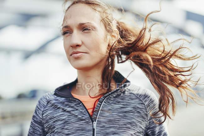 Retrato de una corredora femenina con pelo de mosca en la pasarela de la ciudad - foto de stock