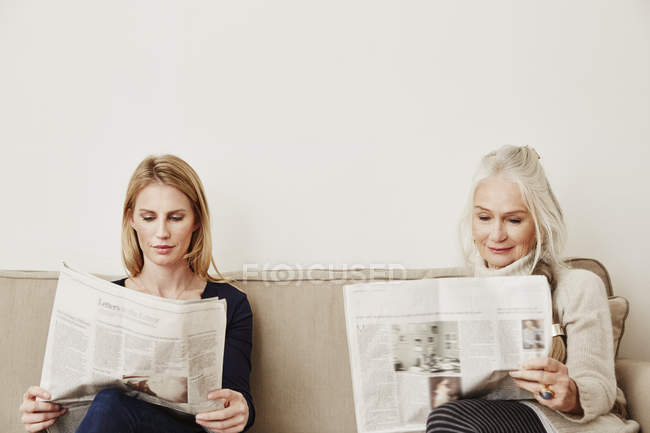 Senior and mid adult women reading newspapers — Stock Photo