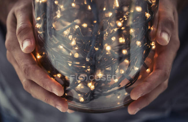 Cropped view of hands holding glass jar filled with decorative lights — Stock Photo