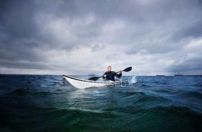 Man rowing in kayak on the ocean — Stock Photo