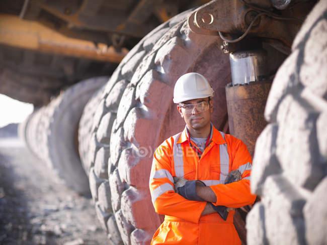 Portrait of miner standing next to  dumper truck tyres in opencast coalmine — Stock Photo