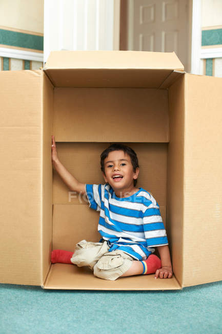 Boy playing in cardboard box — Stock Photo