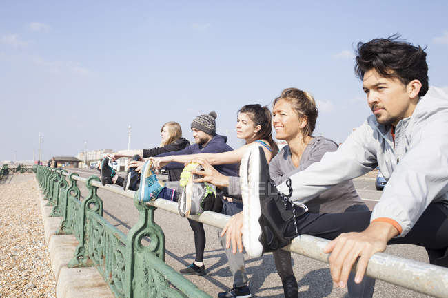Five male and female runners warming up, touching toes at Brighton beach — Stock Photo