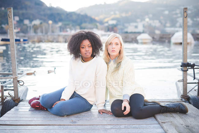Portrait of two female friends sitting on pier, Lake Como, Italy — Stock Photo
