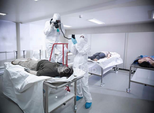 Судебный эксперт фотографирует искусственное тело в морге на тренировочном объекте — стоковое фото