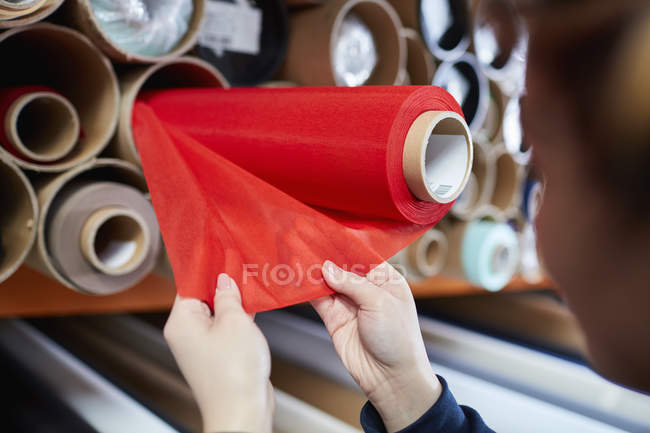 Hands of female worker examining red fabric for roller blind in factory — Stock Photo