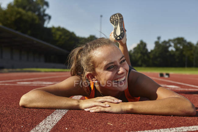 Young female runner lying on front on race track — Stock Photo