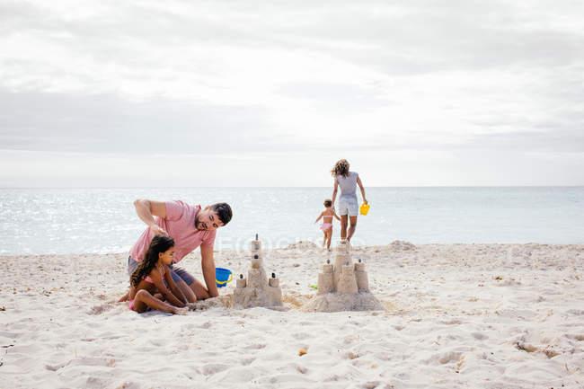 Пара и две девочки, здание Сандкасл на пляж, Тоскана, Италия — стоковое фото