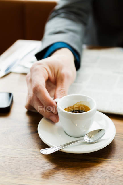 Businessman drinking cappuccino, close-up partial view — Stock Photo