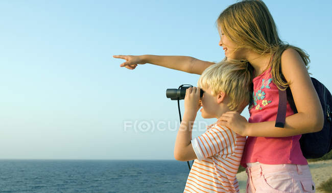 Молода дівчина вказуючи пальцем в той час як хлопчик дивиться в бінокль — стокове фото