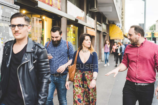 Groupe d'amis marchant sur le trottoir ensemble — Photo de stock