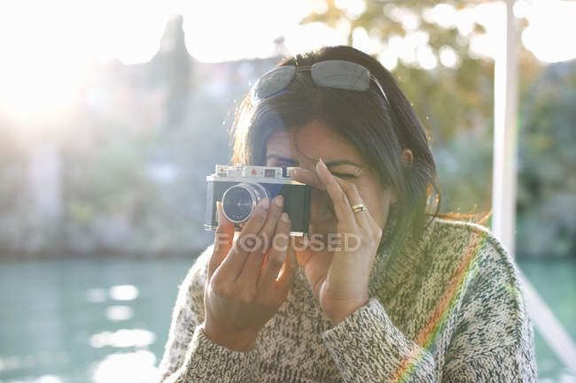 Mature female tourist photographing at Guadalqivir river, Seville, Spain — Stock Photo