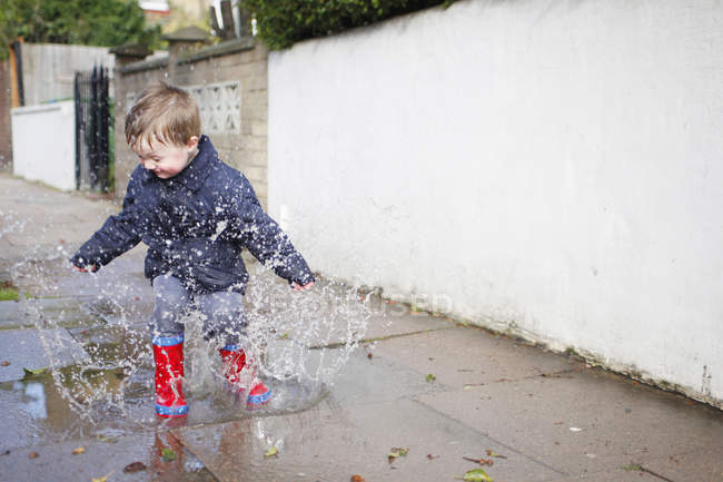 Male toddler in red rubber boots splashing in sidewalk puddle — Stock Photo