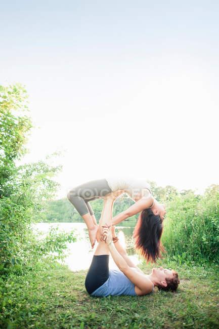 Paar praktiziert Yoga im Garten — Stockfoto