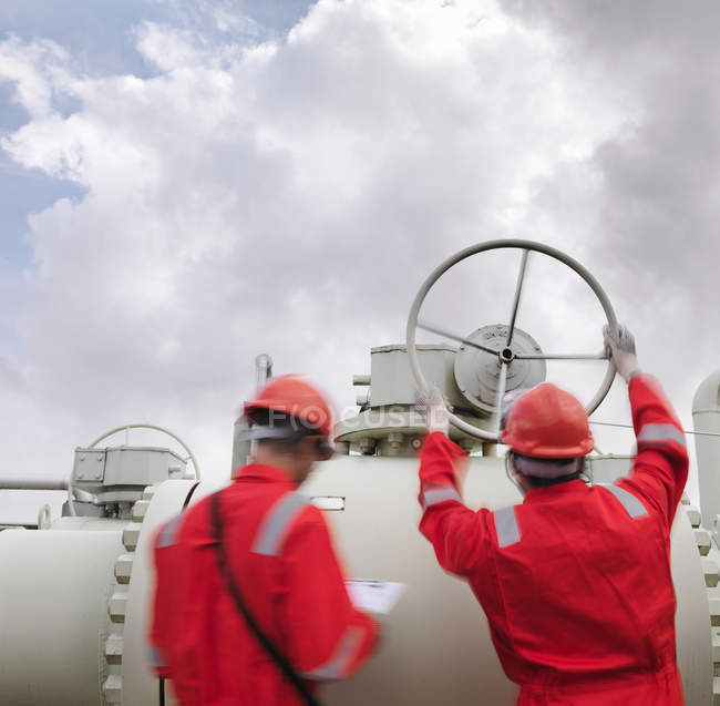 Workers with valve at gas storage plant — Stock Photo