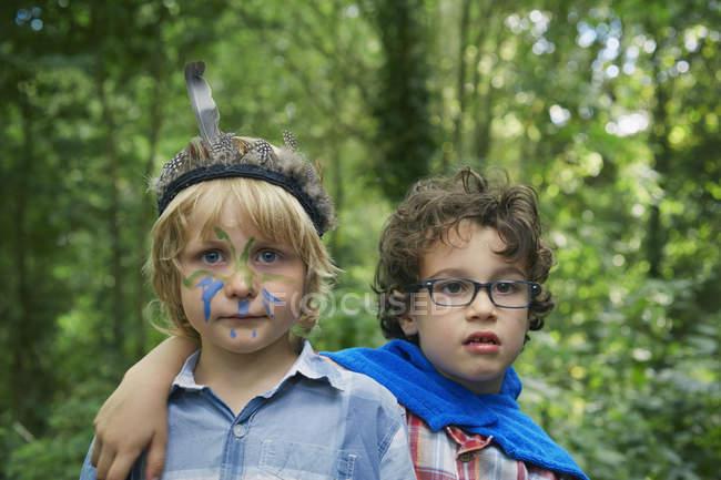 Портрет двух мальчиков в лесу с краской на лице — стоковое фото