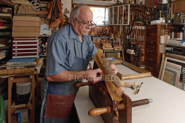 Старший мужчина ремонтирует хрупкий позвоночник антикварной книги в традиционной мастерской по переплетению книг — стоковое фото