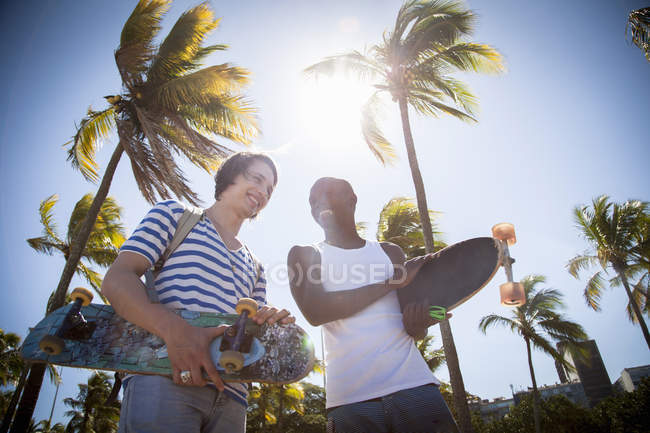 Two men, holding skateboards, walking outdoors — Stock Photo