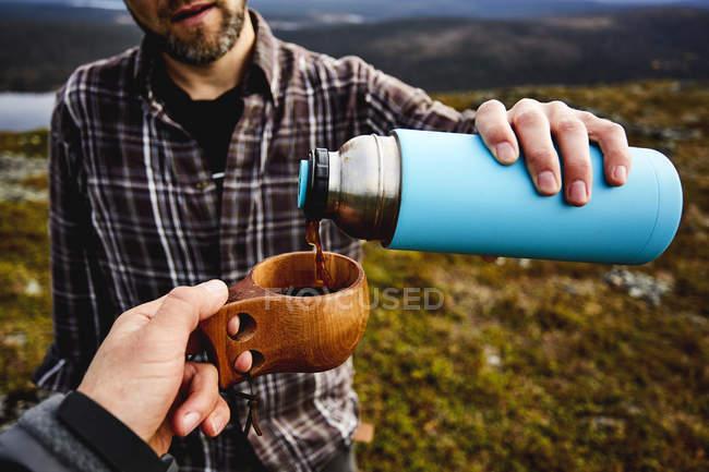 Escursionista versando caffè a tazza per amico — Foto stock